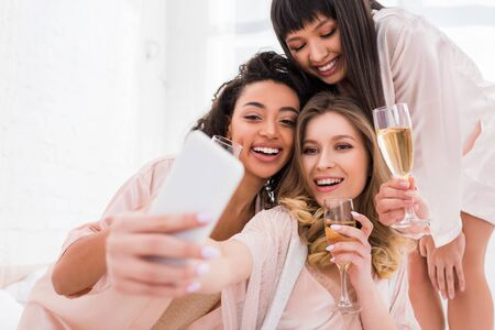 smiling multiethnic girls with champagne glasses taking selfie on smartphone during pajama party Foto de archivo
