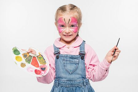smiling child with butterfly painting on face holding palette and paintbrush while looking at camera isolated on white Foto de archivo