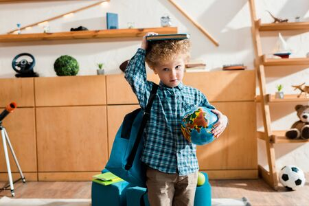 smart and curly kid with backpack holding globe and book above head Imagens