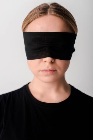 blindfolded young woman isolated on white, human rights concept