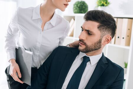 cropped view of secretary with big breast touching shocked businessman in office