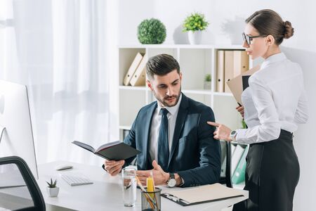 attraktive Sekretärin, die die Hand eines gutaussehenden Geschäftsmannes im Büro berührt Standard-Bild