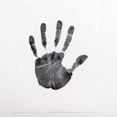 top view of black print of hand on paper isolated on white, human rights concept