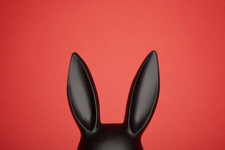 top view of black rabbit mask isolated on red
