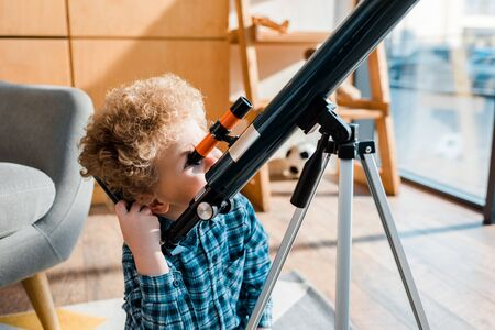 smart child looking through telescope at home