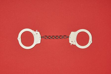 top view of metal handcuffs isolated on red
