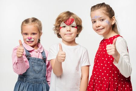 cheerful friends with colorful face paintings showing thumbs up while looking at camera isolated on white Stock Photo
