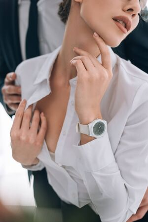 cropped view of businessman touching secretary with big breast in office