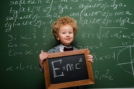 happy kid in suit and bow tie holding small blackboard with formula near chalkboard