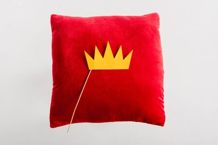 top view of paper crown on red pillow isolated on white