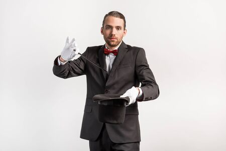 magician in suit making trick hat and wand, isolated on grey