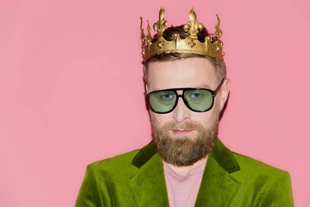 handsome man in velour jacket and crown looking at camera isolated on pink