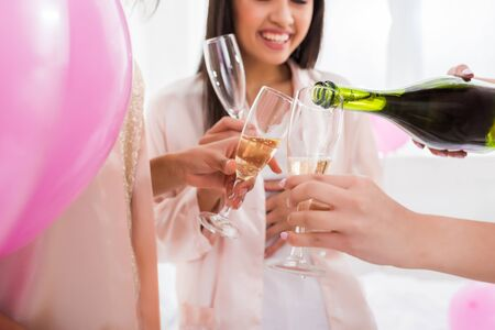 cropped view of happy girls pouring champagne from bottle into glasses on bachelorette party with pink balloons