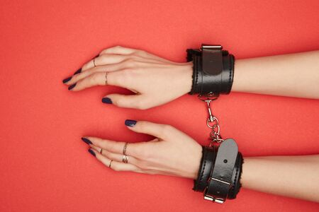 cropped view of woman in black handcuffs isolated on red Stock Photo