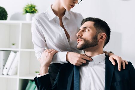 cropped view of secretary with big breast hugging handsome businessman in office