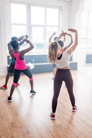Back view of multicultural dancers with raised hands exercising in dance studio