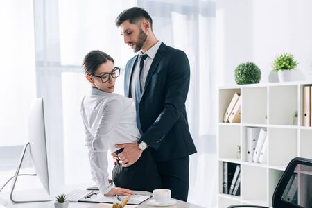 handsome businessman hugging attractive secretary on table in office