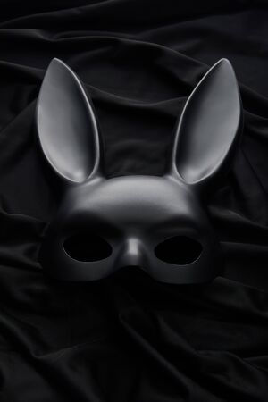 top view of rabbit mask on black textile background