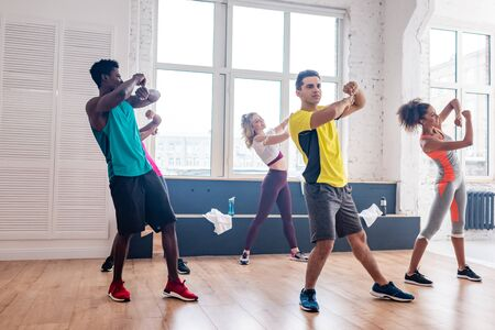 Young multicultural dancers exercising movements in dance studio