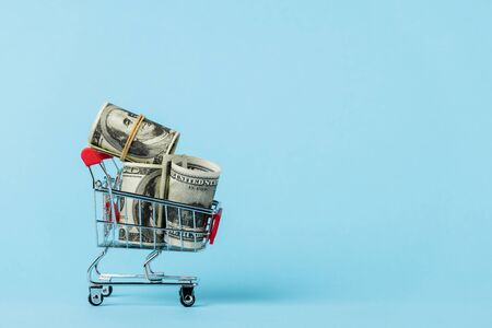 toy shopping cart with dollar banknotes on blue, leasing concept Stock Photo
