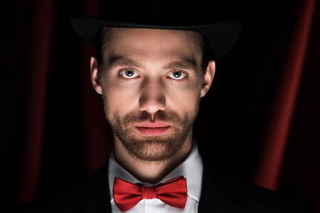 handsome magician in suit and bow tie in circus with red curtains Banque d'images