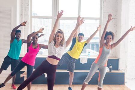 Selective focus of multicultural dancers with hands in air training together in dance studio