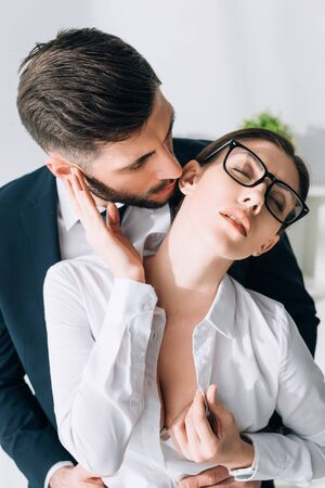 businessman kissing attractive secretary with big breast in office