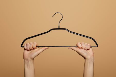 cropped view of woman holding empty hanger isolated on beige