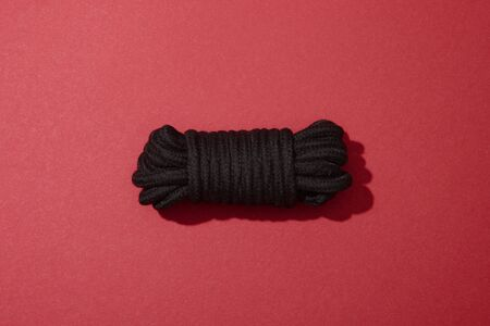 top view of black rope on red background