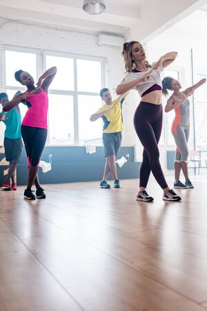 Low angle view of attractive trainer exercising with multicultural dancers in studio Banque d'images