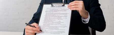 panoramic shot of realtor holding clipboard with lease agreement lettering on white Stock Photo