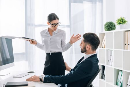businessman touching butt of shocked secretary with folder in office 写真素材