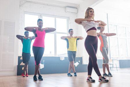 Inquadratura dal basso dell'allenatore sorridente che si esercita con ballerini multiculturali in studio di danza