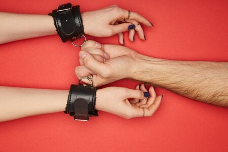 cropped view of man holding handcuffs on woman isolated on red