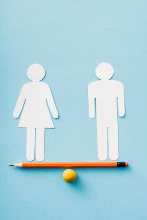 paper figures of couple as gender equality on pencil with ball isolated on blue, equality concept