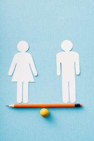 Papierfiguren des Paares als Gleichstellung der Geschlechter auf Bleistift mit Kugel isoliert auf Blau, Gleichstellungskonzept