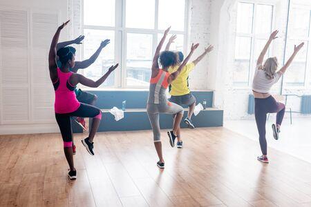 Vista posterior de bailarines multiculturales haciendo ejercicio en el estudio de danza Foto de archivo