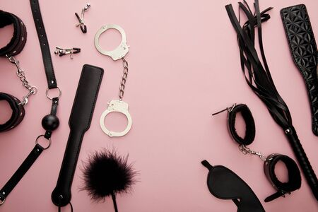 top view of black sex toys on pink background 스톡 콘텐츠