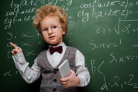 Niño inteligente en traje y pajarita sosteniendo el teléfono inteligente y apuntando con el dedo cerca de la pizarra con fórmulas matemáticas