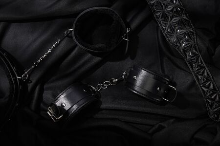 top view of handcuffs and paddle on black textile background
