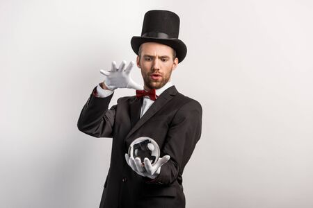 focused professional magician holding magic ball, isolated on grey