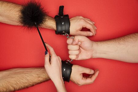 cropped view of men and woman with handcuffs and feather tickler isolated on red