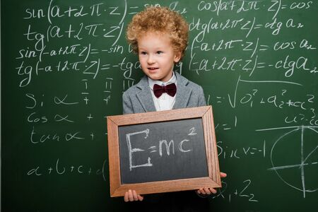 smart child in suit and bow tie holding small blackboard with formula near chalkboard