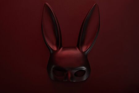 top view of rabbit black mask in dark lighting on red background