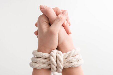 cropped view of woman with rope on praying hands isolated on white, human rights concept