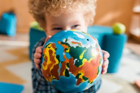 selective focus of smart kid covering face with globe 免版税图像