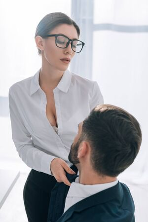 sexy secretary with big breast pulling tie of businessman in office 스톡 콘텐츠