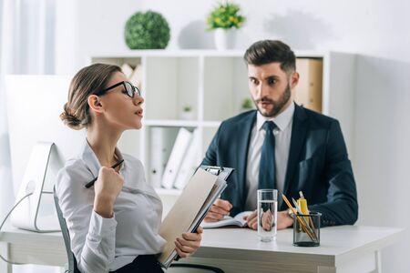 Selektiver Fokus der Sekretärin, die einen schockierten Geschäftsmann im Büro verführt
