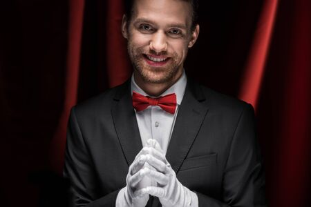 smiling gentleman in suit, bow tie and gloves in circus with red curtains