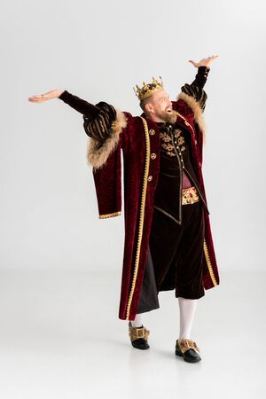 happy king with crown and outstretched hands on grey background